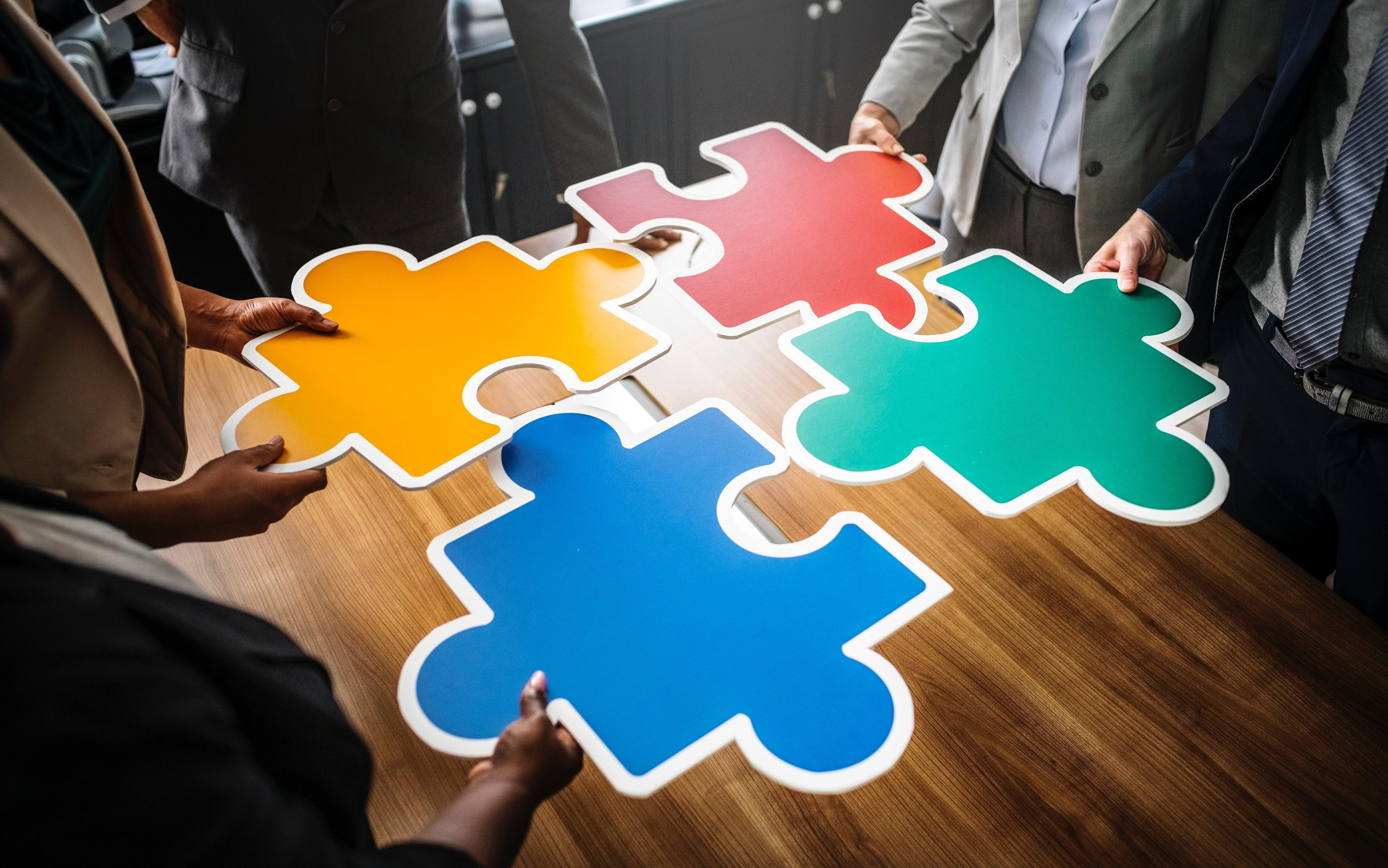 three-people-holding-puzzles-and-assembling-on-brown-wooden-table